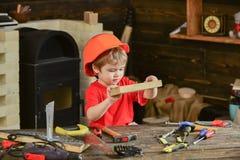Enfant jouer mignon de casque comme constructeur ou réparateur, en réparant ou handcrafting Concept Handcrafting Enfant en bas âg Images libres de droits
