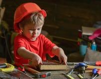 Enfant jouer mignon de casque comme constructeur ou réparateur, en réparant ou handcrafting L'enfant en bas âge sur le visage occ Photographie stock