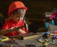 Enfant jouer mignon de casque comme constructeur ou réparateur, en réparant ou handcrafting L'enfant en bas âge sur le visage occ Image stock