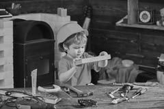 Enfant jouer mignon de casque comme constructeur ou r?parateur, en r?parant ou handcrafting Concept Handcrafting Enfant en bas ?g photographie stock libre de droits
