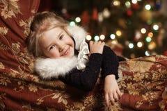 Enfant joyeux avec un cadeau près de l'arbre de Noël Photos stock