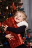 Enfant joyeux avec un cadeau près de l'arbre de Noël Photo stock