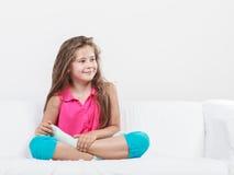 Enfant joyeux heureux de petite fille s'asseyant sur le sofa Photographie stock