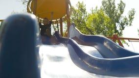 Enfant joyeux heureux glissant vers le bas une glissière bleue sur un terrain de jeu en parc banque de vidéos
