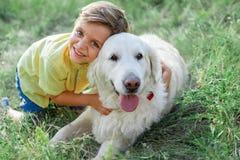 Enfant joyeux jouant avec son animal familier sur le pré Photographie stock
