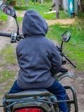 Enfant joyeux s'asseyant sur une moto photo stock