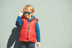 Enfant ?l?gant dans des lunettes de soleil ? la mode mode de gosses Petit gar?on blondy mignon dans la position rouge de veste au photo stock