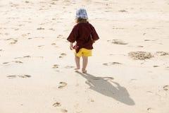 Enfant laissant de petites étapes dans le sable, jouant nu-pieds images libres de droits