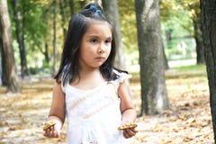 Enfant latin sérieux tenant deux moitiés d'un biscuit dans chaque main Photos libres de droits