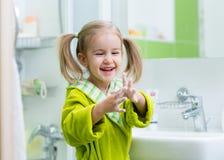 Enfant lavant et montrant les mains savonneuses image stock