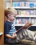 Enfant lisant un livre à la bibliothèque Photographie stock libre de droits