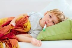 Enfant malade avec l'écoulement nasal et chaleur de fièvre se trouvant sur le divan à la maison photographie stock libre de droits