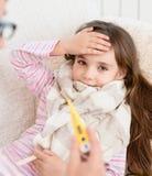 Enfant malade avec la grosse fièvre s'étendant dans le lit et la mère prenant la température Photos libres de droits