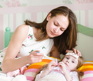 Enfant malade avec la grosse fièvre s'étendant dans le lit et la mère prenant la tempera Image stock