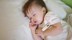 Enfant malade avec le thermomètre dormant sur le lit blanc la température de l'enfant est mesurée utilisant le thermomètre dans u banque de vidéos