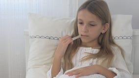 Enfant malade dans le lit, enfant malade avec le thermomètre, fille de souffrance, médecine de pilules banque de vidéos