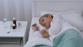 Enfant malade dans le lit, enfant malade avec le thermomètre, fille dans l'hôpital, médecine de pilules banque de vidéos