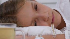 Enfant malade dans le lit, enfant malade avec le thermomètre, petite fille dans l'hôpital, médecine de pilules banque de vidéos