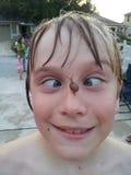 Enfant maladroit regardant bigle un escargot sur son nez Photos libres de droits