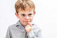 Enfant malfaisant avec les taches de rousseur de froncement de sourcils ayant le doute pour la solution sérieuse Photos libres de droits