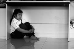 Enfant malheureux de garçon de renversement triste se cachant sous la table Image stock