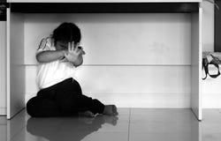 Enfant malheureux de garçon de renversement triste se cachant sous la table Images libres de droits