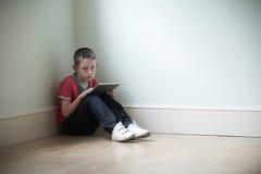 Enfant malheureux s'asseyant dans la chambre avec la Tablette de Digital Image libre de droits