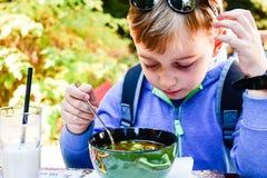 Enfant mangeant d'une soupe photos stock