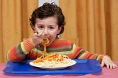 Enfant mangeant dans sa maison Photographie stock libre de droits