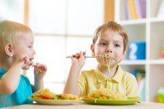 Enfant mangeant de la nourriture saine à la maison ou au service de garderie Photographie stock libre de droits