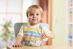 Enfant mangeant de la nourriture saine à la pièce de crèche Photographie stock libre de droits