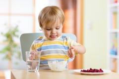 Enfant mangeant de la nourriture saine avec une cuillère Photo stock