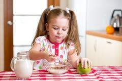 Enfant mangeant de la nourriture saine dans la cuisine Photos libres de droits