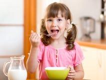 Enfant mangeant de la nourriture saine dans la cuisine Photos stock
