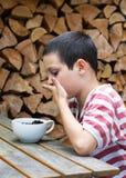 Enfant mangeant des baies à la table de jardin Photos libres de droits