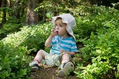 Enfant mangeant des myrtilles photo stock