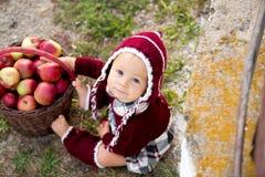 Enfant mangeant des pommes dans un village en automne Petit jeu de bébé garçon photographie stock