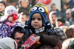 Enfant mangeant du maïs éclaté dans une rue complètement des personnes Photo stock