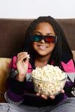 Enfant mangeant du maïs éclaté observant le film 3d Images libres de droits