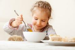 Enfant mangeant du potage à la maison Photos stock
