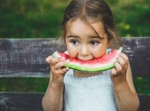 enfant mangeant la pastèque dans le jardin Les enfants mangent du fruit dehors Casse-croûte sain pour des enfants Beau fond, fill photo stock