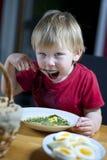 Enfant mangeant la soupe et le pain croustillant ? ?pinards Photographie stock libre de droits