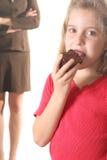 Enfant mangeant le 'brownie' - maman pas photographie stock