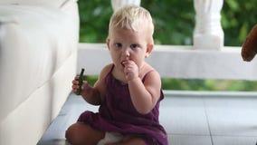 Enfant mangeant le concombre se tenant se penchant sur le sofa banque de vidéos