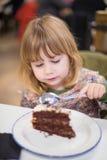 Enfant mangeant le morceau de gâteau de chocolat au restaurant Images libres de droits