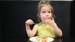 Enfant mangeant le riz et les champignons cuits avec une cuillère sur un fond noir à la table noire clips vidéos