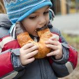 Enfant mangeant sur la rue Image stock