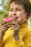 Enfant mangeant un beignet rose photo stock