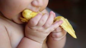 Enfant mangeant une banane avec la peau banque de vidéos