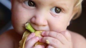 Enfant mangeant une banane avec la peau clips vidéos
